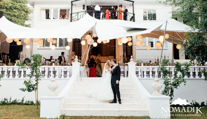 A white stretch tent creates the perfect space for making a garden wedding come alive